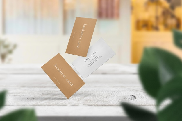 Clean minimal business cards mockup float top table in front of the cafe.