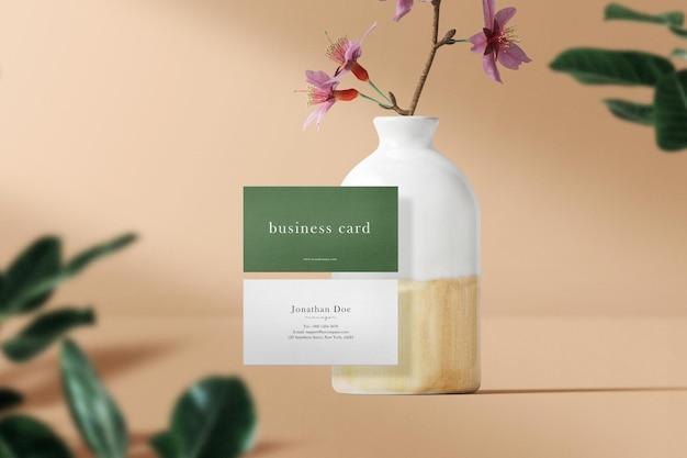 Чистый минимальный макет визиток, плавающий на вазе, и цветы с листьями