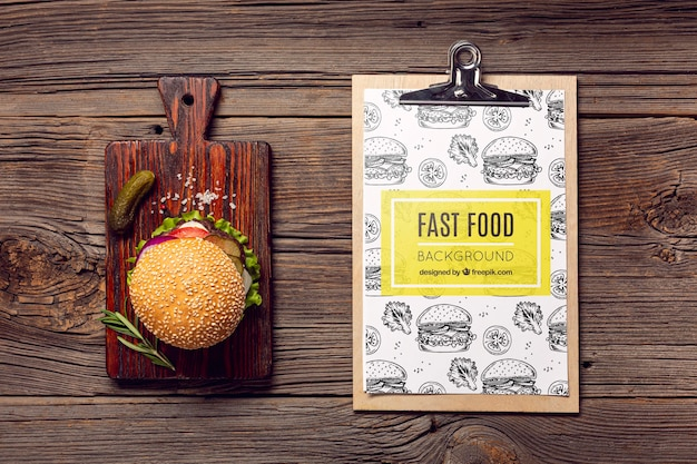 Clipboard and burger on wooden background