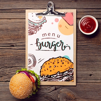 Clipboard menu burger and food on wooden background