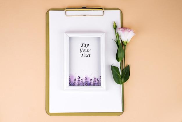 トルコギキョウの花とベージュの紙に白いフレームを使用してクリップボード、フラットレイアウト。