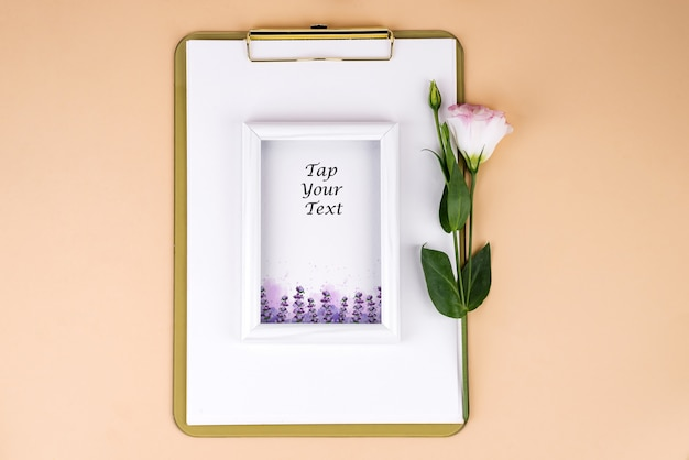 Clipboard with eustoma flower and white frame on beige paper, flat lay.