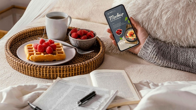 Close up on breakfast in bed with phone screen mockup