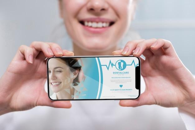 Dentista del primo piano che tiene un modello dello smartphone