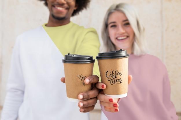 Крупный план друзей с толстовками и кофейной чашкой