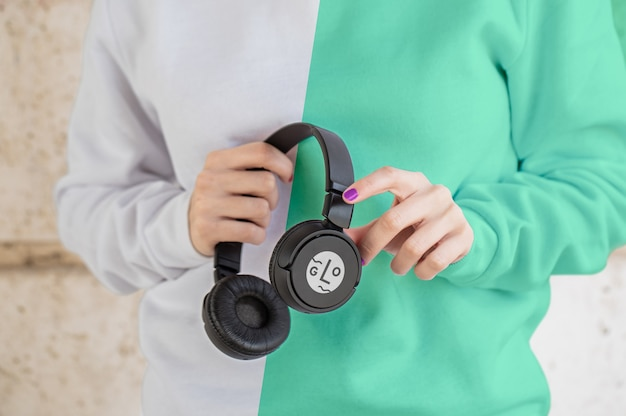 Close-up girl with hoddie holding headphones