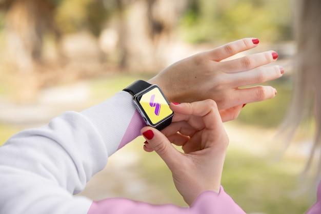 Ragazza del primo piano con la maglia con cappuccio che esamina smartwatch