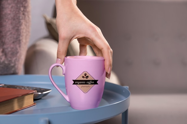 Close-up hand holding coffee mug Free Psd