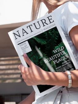 La mano del primo piano che tiene una rivista della natura deride su