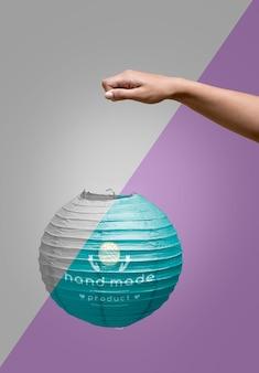 Рука крупным планом держит бумажную лампу