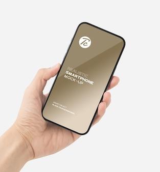 あなたのデザインのスマートフォンのモックアップを持っている手を閉じる