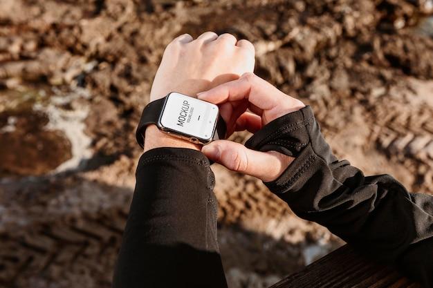 Chiuda sulla mano che indossa il mockup dell'orologio