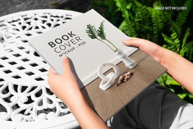 Close up on hands holding a book mockup Premium Psd
