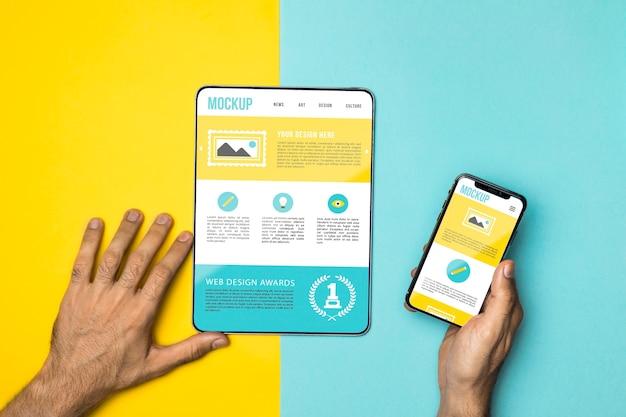 Mani del primo piano che tengono telefono e tablet