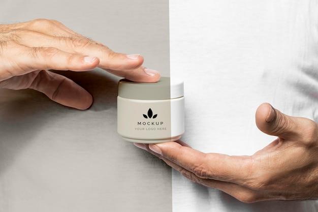 Chiudere le mani con il contenitore della crema