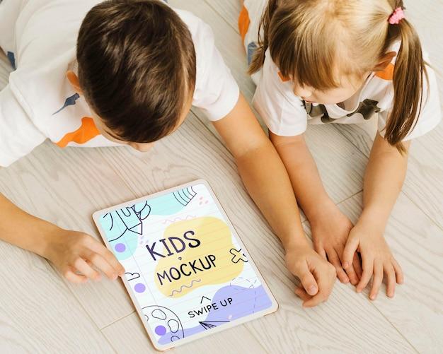 Chiudere i bambini sul pavimento con il tablet