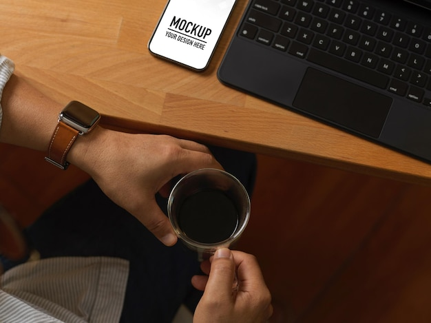 Close up of male hands holding coffee cup at workspace with smartphone mockup
