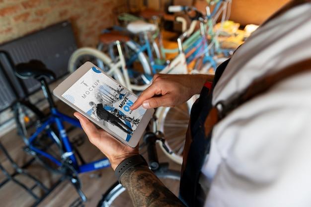 Primo piano sull'uomo nel suo laboratorio che lavora su un modello di dispositivo digitale
