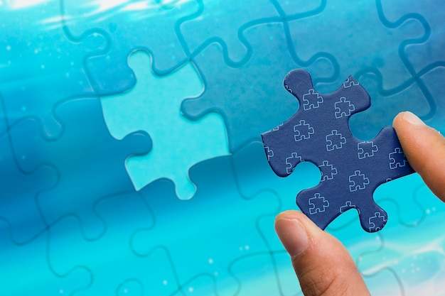 Close-up man holding jigsaw piece of puzzle