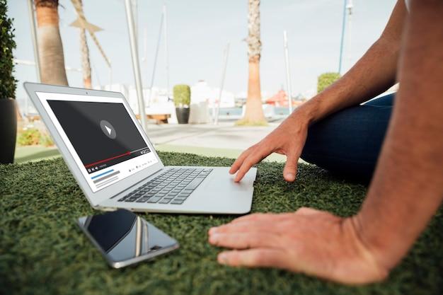 Uomo del primo piano all'aperto con il computer portatile e il cellulare