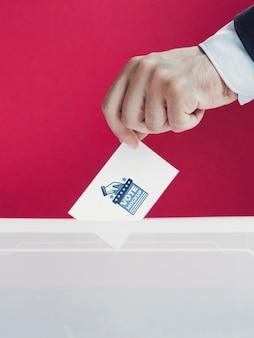 Uomo del primo piano che mette modello di scheda elettorale nella casella