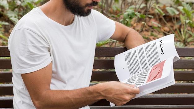 Close up man on street reading book