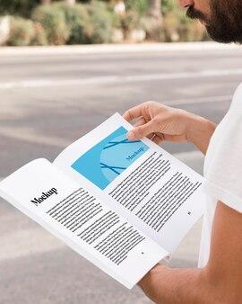 Close up uomo sulla strada leggendo il libro