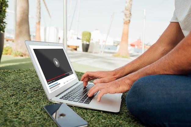 Uomo del primo piano con il computer portatile e il cellulare