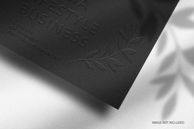 Макет логотипа с тиснением на черной бумаге крупным планом