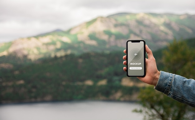 Close up mockup of a hand holding mobile phone on mountains background