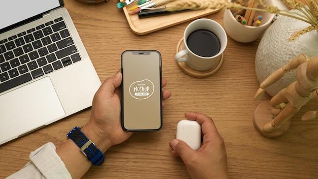 ホームオフィスの机の上で彼の手にスマートフォンを持っているビジネスマンのクローズアップ