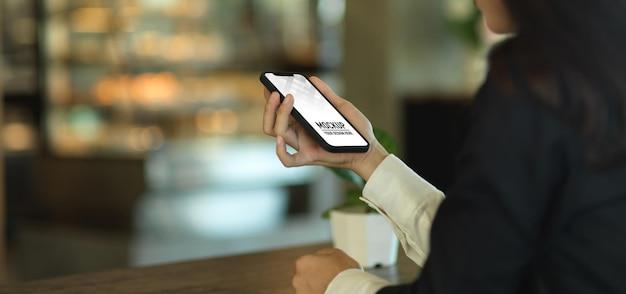 スマートフォンのモックアップを持っている実業家の手のクローズアップ