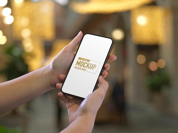 モックアップ画面でスマートフォンを保持している女性の手のクローズアップ