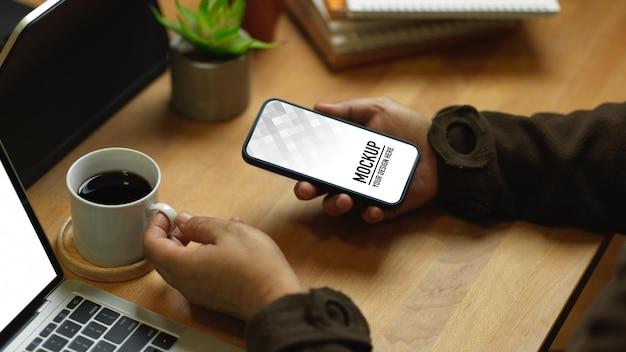 Крупным планом мужской руки, держащей макет смартфона