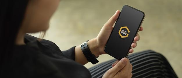 スマートフォンのモックアップを保持している女性の手にクローズアップ