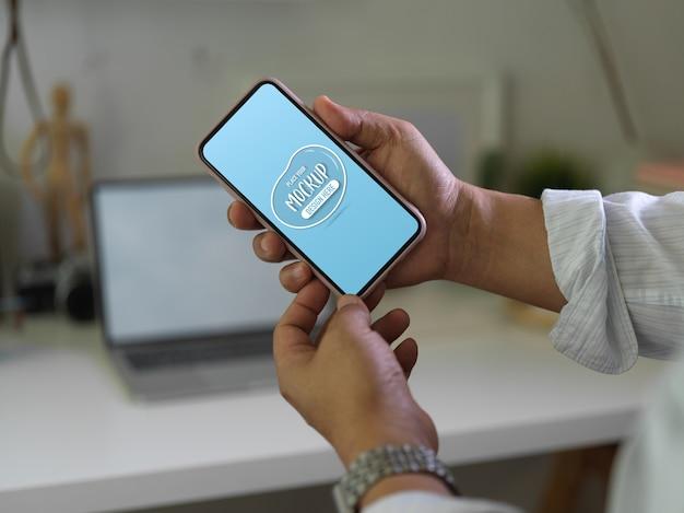 スマートフォンの画面のモックアップを両手でクローズアップ