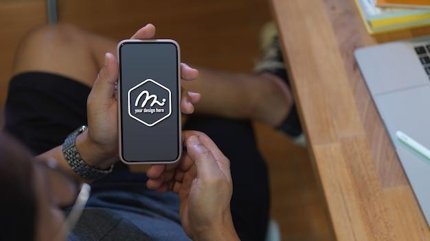 Крупным планом на руках, держащих макет экрана смартфона