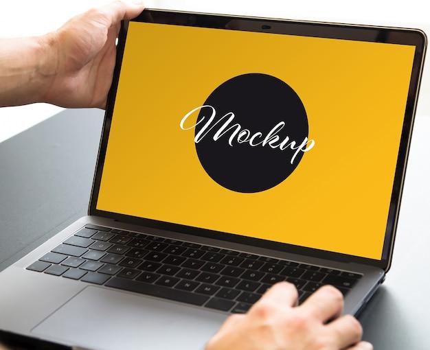 ノートパソコンのモックアップを開く手でクローズアップ