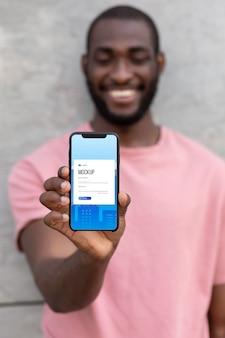 スマートフォンのモックアップを使用して男性にクローズアップ