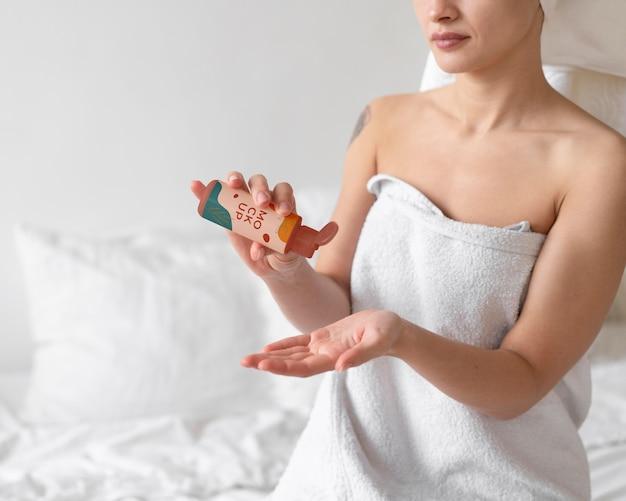 Крупным планом на женщину, держащую макет бутылки с таблетками