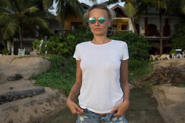 T- 셔츠 모형과 함께 해변에서 여자에 가까이
