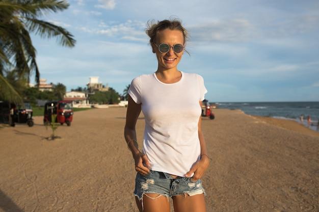 Tシャツのモックアップでビーチの女性にクローズアップ