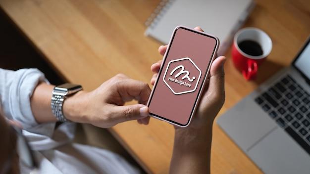 Крупным планом работника, использующего макет телефона для исследования