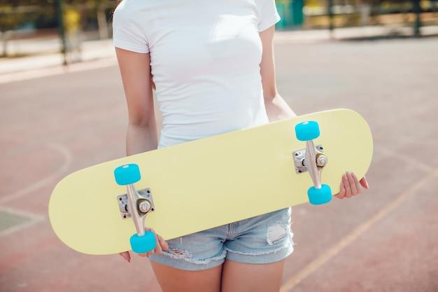 스케이트 보드 모형을 들고 젊은 여자에 가까이