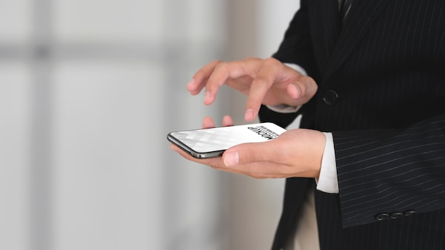 Close up view of businessman in black suit hands using smartphone mockup