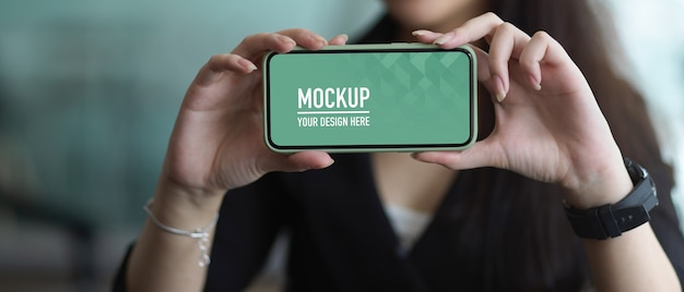 Close up view of businesswoman showing horizontal smartphone mockup