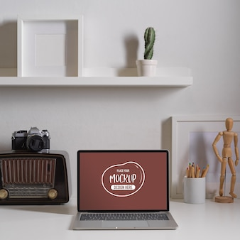 Close up view of contemporary worktable with mock up laptop, vintage radio and decorations