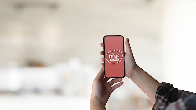 Close up view of female hand holding mock up smartphone