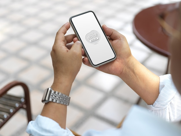 Close up view on hands holding smartphone with screen mockup