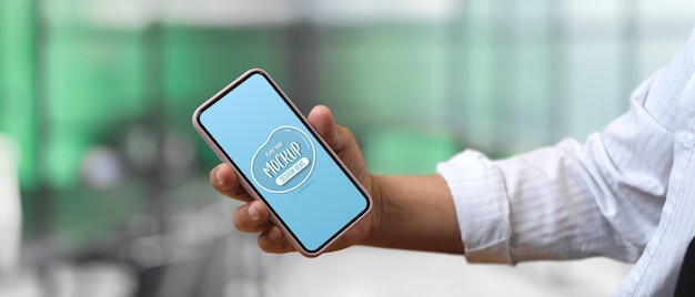Close up view of male hand holding mock up smartphone in blurred office  background